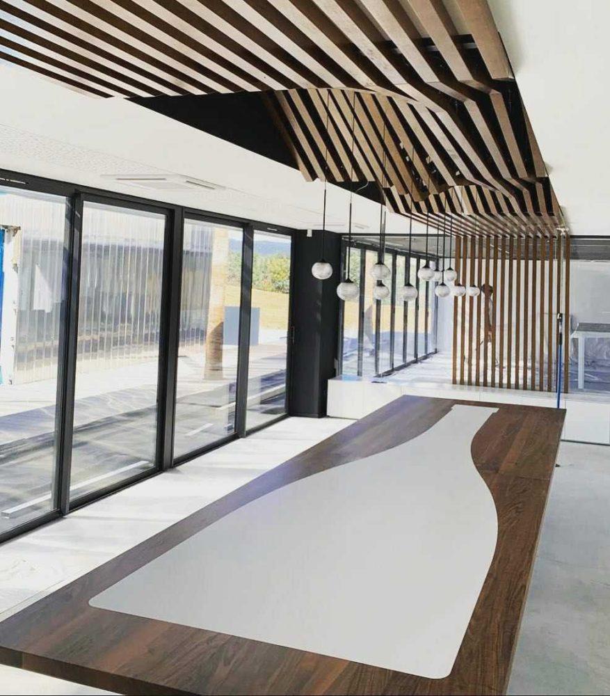 Table en noyer avec une incrustation corian® et plafond déstructuré suspendu, claustra en noyer massif,